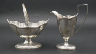 A Victorian silver handled sugar bowl and cream jug with linear detailing around the scalloped rim