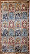 A Persian Qum with repeating panels containing floral and boteh motifs enclosed by a stylised