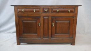 A 18th century French Provincial oak side cabinet with pair of frieze drawers and central narrow