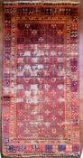 An antique Tabat carpet with repeating gul motifs across the deep red field contained within a