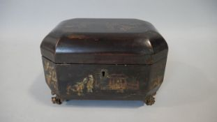 A Georgian jappaned lacquered lidded box with hand gilded and painted decoration on carved gilt wood