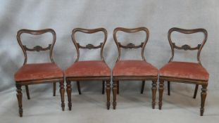 A set of four mid 19th century rosewood dining chairs with shaped backs above drop in seats on