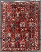 A Persian Bakhtiar carpet with repeating panels across the field with palmette and boteh motifs