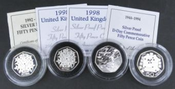 Four proof fifty pence coins. Including a 1998 Silver proof 50p coin for the 25th anniversary of the