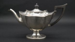 A Victorian silver tea pot with ebony handle and finial with scalloped design. Hallmarked: TB for