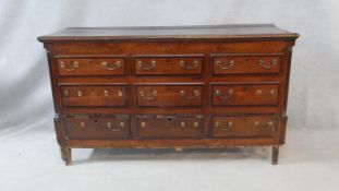 A Georgian oak and mahogany crossbanded mule chest with hinged lidded top and coffer section faced
