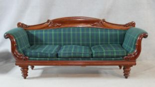 An early Victorian mahogany framed three seat sofa with carved scrolling foliate decoration and