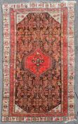 An antique Persian Malayer carpet with central hooked pole medallion on a stylised floral field