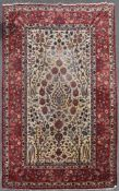 A Persian Isfahan carpet with tree of life design on a cream ground with animal motifs contained