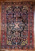 A Persian Hamadan rug with central floral medallion on midnight ground within stylised floral