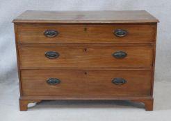 A Georgian mahogany chest of three long graduated drawers with original handles on bracket feet. H.