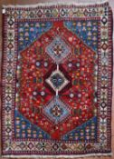 A Persian Shiraz rug with triple pole diamond medallions on a madder ground within sapphire floral