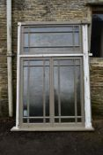 A large painted hardwood window frame of twenty seven double glazed panels with stained glass corner
