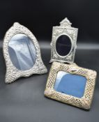 An arched silver floral embossed easel mirror and two other silver embossed mirrors each bearing