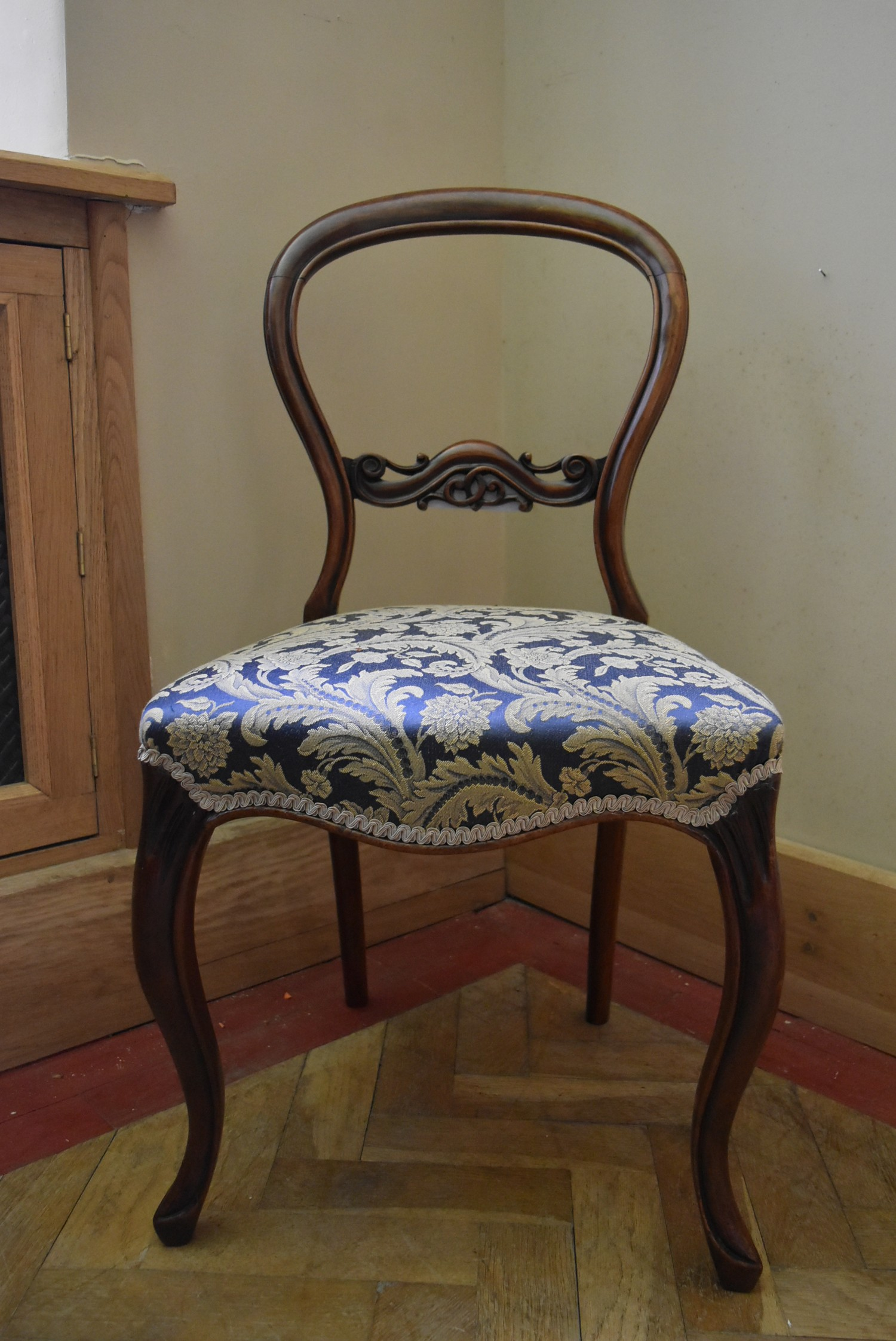 A Victorian carved mahogany balloon back side chair with foliate upholstered stuffover seat on