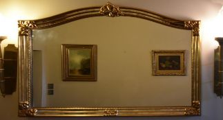 A 19th century style gilt framed overmantel mirror with arched plate and floral cresting. H.90cm W.