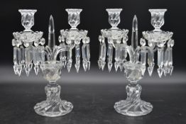 A pair of clear glass twin branch candelabras with crystal drops on spiral twist base. H.34cm W.24cm