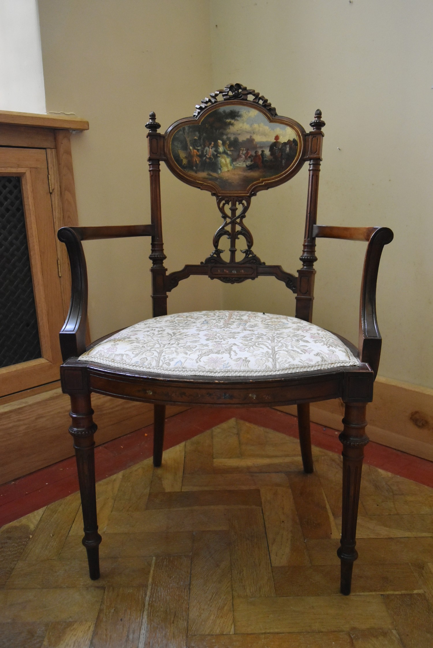 A late 19th century carved walnut salon armchair with hand painted back panel on fluted tapering