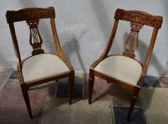 A pair of early 19th century walnut dining chairs with satinwood scroll inlay to the back rail and