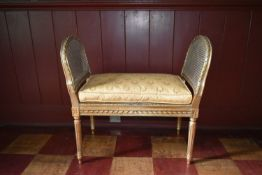 A Louis XVI style gilt framed window seat with caned seat and sides fitted with damask squab