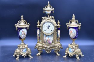 A French style brass cased clock garniture with urn finial and blue glaze with decorative panels