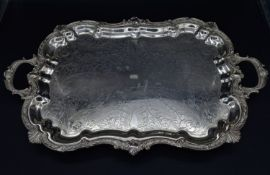 A silver plated twin handled tray with shaped Rococo scrolling and shell motif rim sitting on scroll