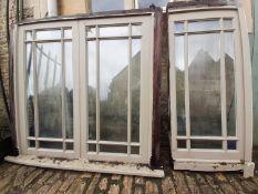 A painted hardwood window frame of eighteen double glazed panels and a similar single nine panel