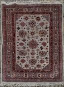 A Eastern carpet with repeating floral motifs across the fawn field within stylised geometric