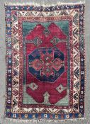 A Kazak rug with central midnight medallion on madder ground contained by stylised spandrels
