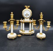 A French neoclassical style clock garniture in gilt metal and marble with a pair of three branch