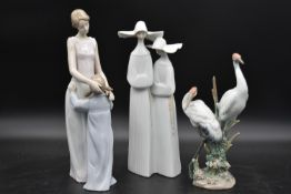 Three Lladro figure groups; mother and child, nuns and cranes amongst the bulrushes. H.37cm (