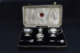 A cased silver cruet set to include shaker, a salt and a mustard jar along with matching spoons,
