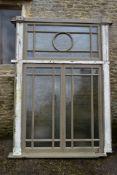 A large painted hardwood window frame of twenty nine double glazed panels with stained glass
