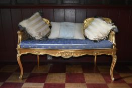 A Louis XV style double chair back carved giltwood window seat with double caned back and damask