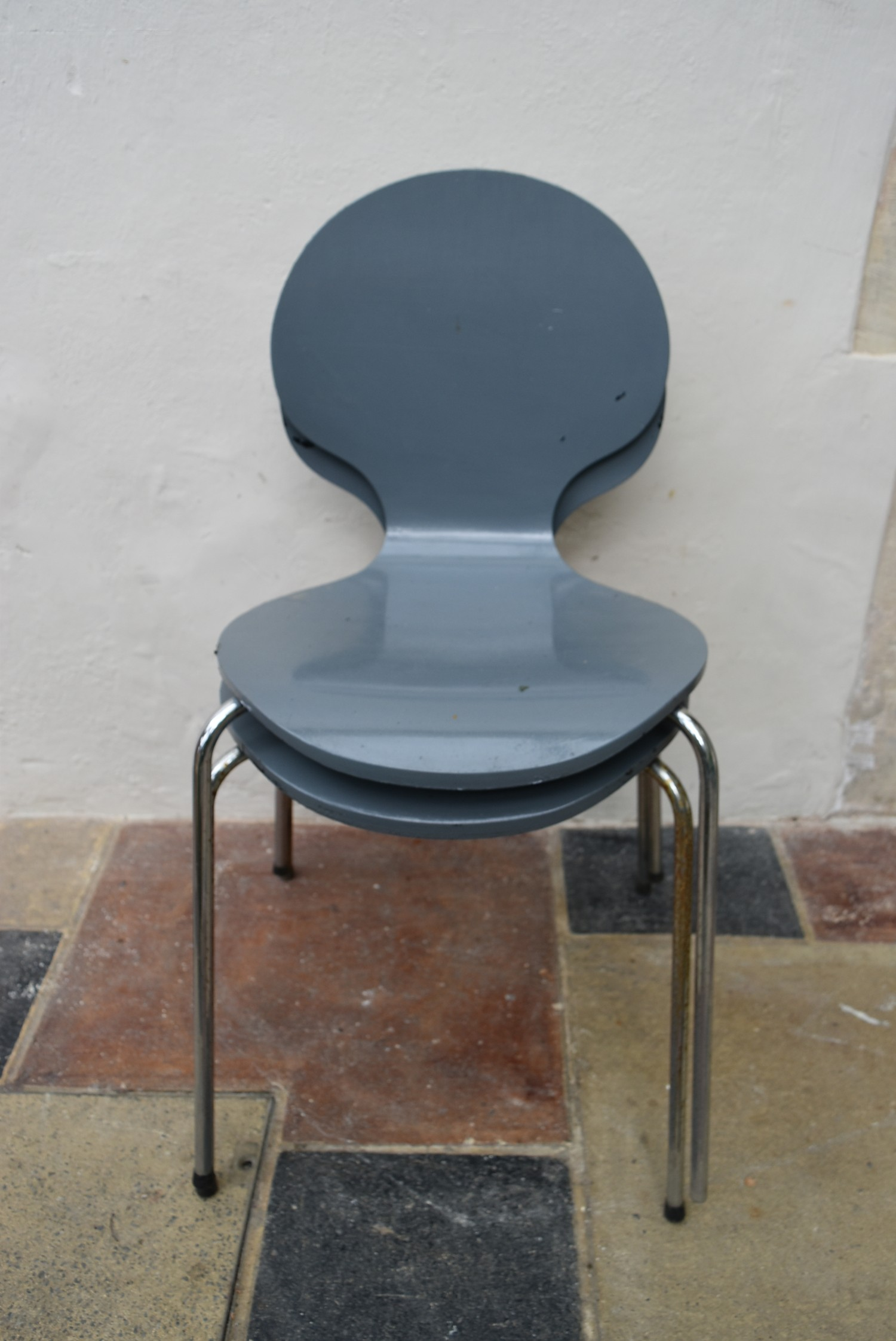 A pair of Arne Jacobsen style painted laminated dining chairs on chrome base. H.82 W.40 D.42cm