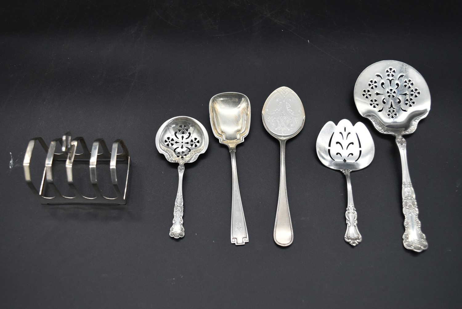 A collection of five 19th century and later English silver spoons along with a silver toast rack,