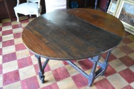 An antique oak drop flap dining table fitted with end drawer on turned and stretchered gateleg