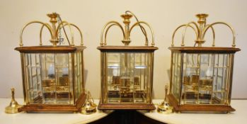 A set of three contemporary brass and oak framed ceiling lanterns in the 19th century style each