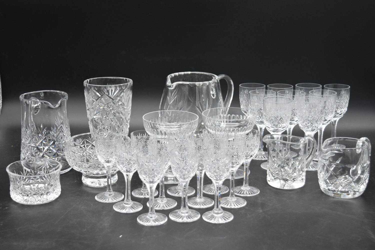 An extensive suite of cut crystal to include port and sherry glasses, champagne cups, vases, water