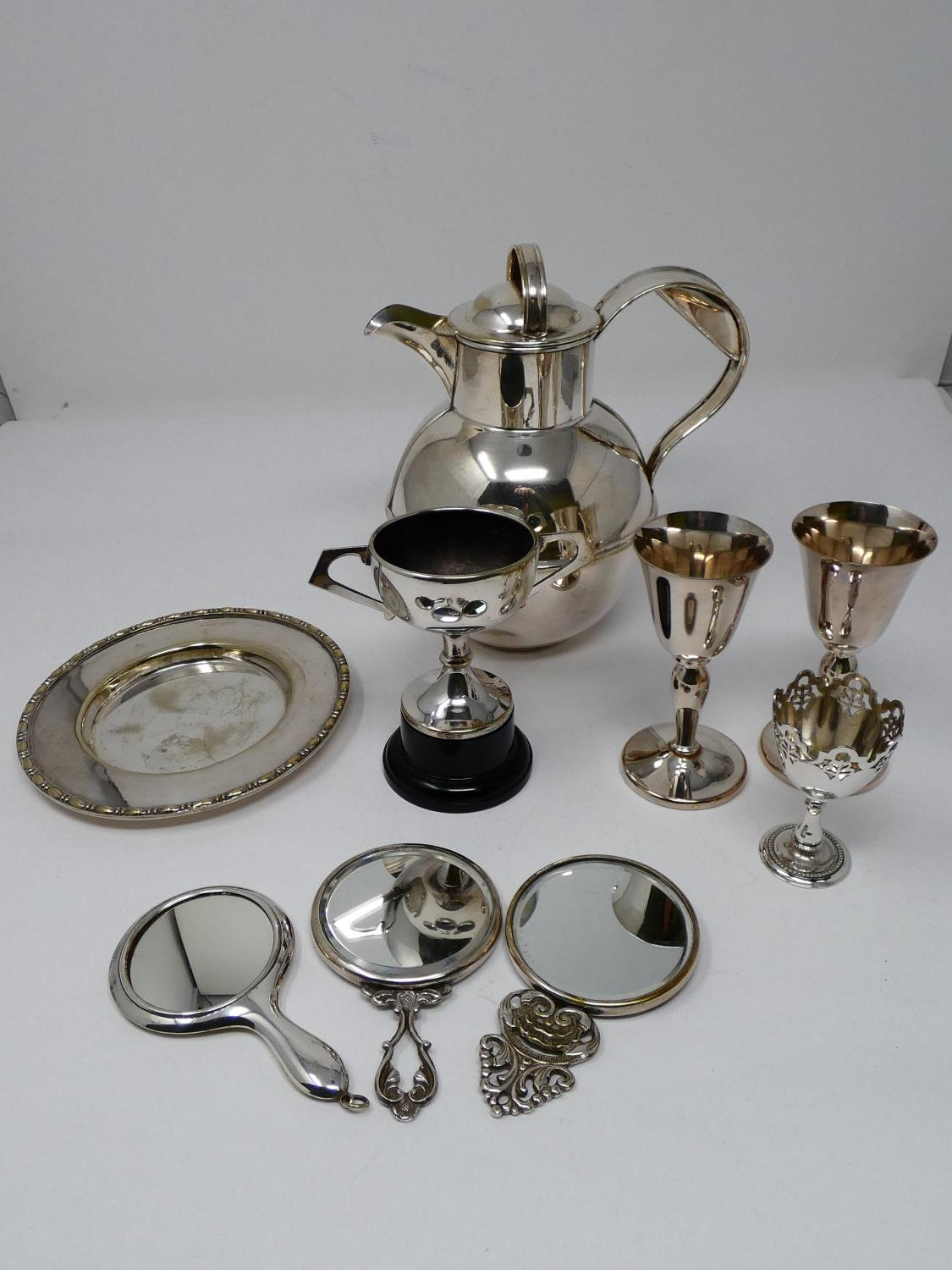 A collection of silver plated items; a hot water jug, trophy cups, card tray and hand mirrors (one