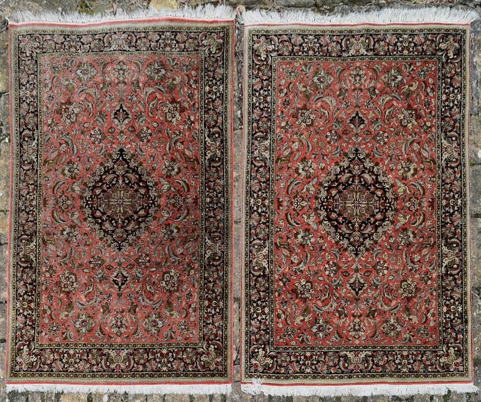 A pair of silk Persian rugs with central floral pole medallion on a madder ground with scrolling