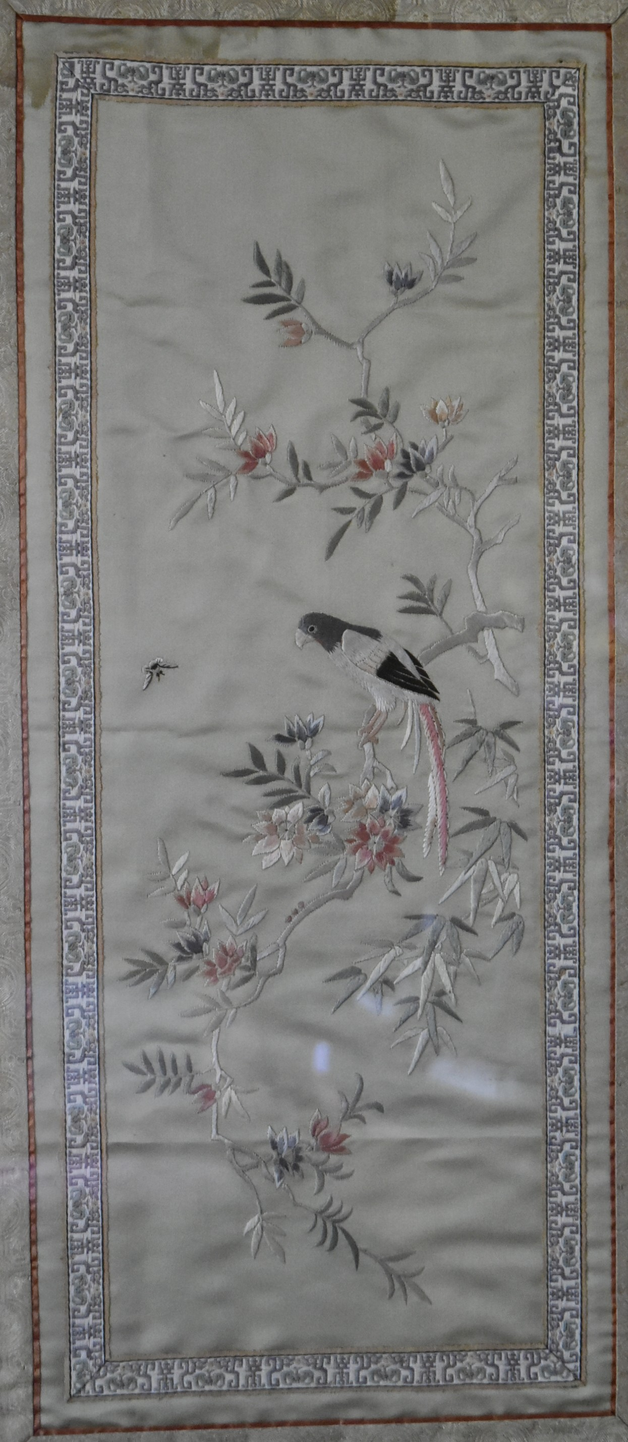 A Japanese framed and glazed silk work embroidery of a parakeet on a branch with blossom contained