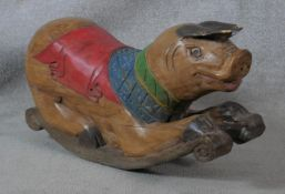 An Eastern carved and painted hardwood polychrome child's rocking pig. H.40 L.80cm