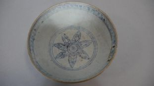 An Oriental blue and white ceramic glazed bowl with floral motif to the inside centre and stylised