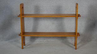 An Arts and Crafts light oak floor standing two tier open bookshelf. H.76.5 W.101.5 D.20.5cm
