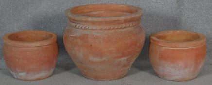 A pair of terracotta garden pots and a similar larger pot. H.32.5 D.40cm (Largest)
