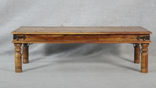 An Indian hardwood metal bound and studded low table on circular section supports. H.41 L.136 W.61.