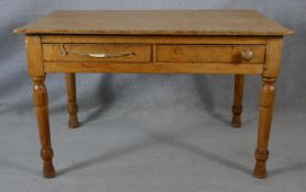 A Victorian pine two drawer side table on turned tapering supports. H.64.5 L.121 W.83cm
