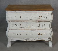 A small distressed painted French bombe style chest with shaped oak top above three long drawers