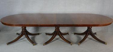 A Georgian style mahogany triple pillar dining table with two extra leaves on quadruped swept